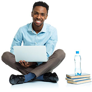 Young man sitting cross legged with laptop in lap.