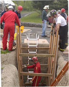 Image of firefighter climbing down ladder into a hole in the ground