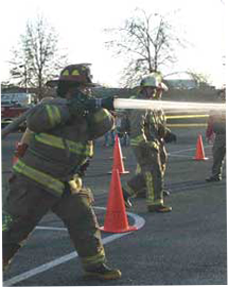 Image of firefighter with hose spraying water