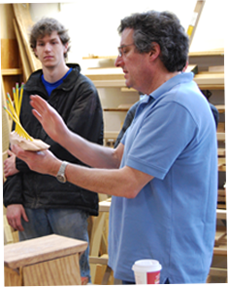 Image of 2 men in classroom with a handful of pencils