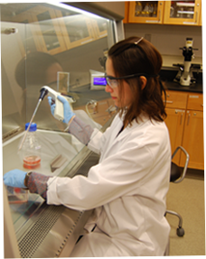 Image of female student with lab coat working in lab