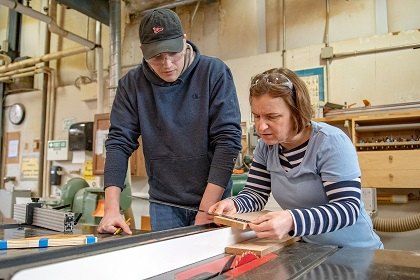 Professor and student working at a table in a woodshop