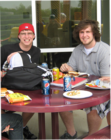 Image of 2 male students sitting outside eating