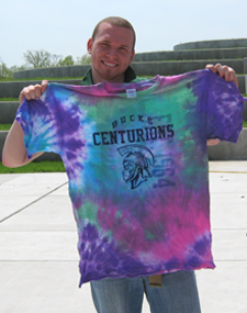 Image of male holding tie dyed shirt up