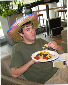 Image of male student eating with sombrero on